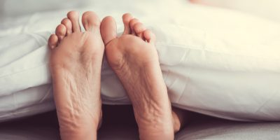 Beautiful feet of sleeping woman under the blanket on her bed. Bedroom on background.